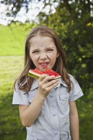 Germany,Bavaria,Girl Eating Watermelon In Park,Portrait