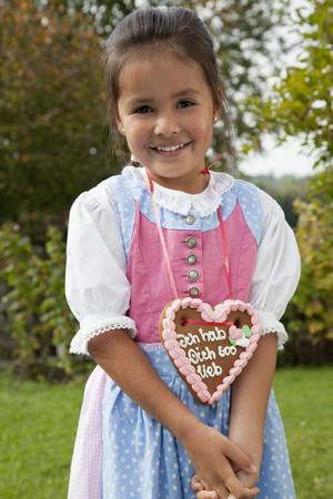 Germany,Bavaria,Huglfing,Girl With Gingerbread Heart In Garden,Smiling,Portrait