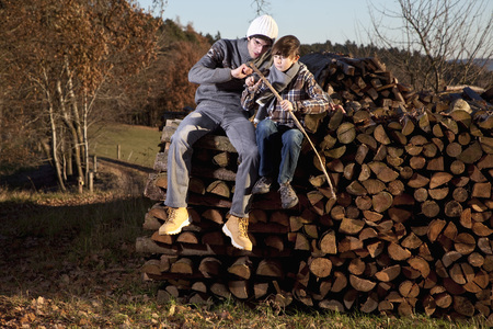 Germany,Bavaria,Father And Son Sitting On Wood And Cutting Stick
