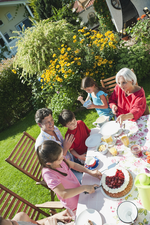 Germany,Bavaria,Family Having Coffee And Cake In Garden,Smiling