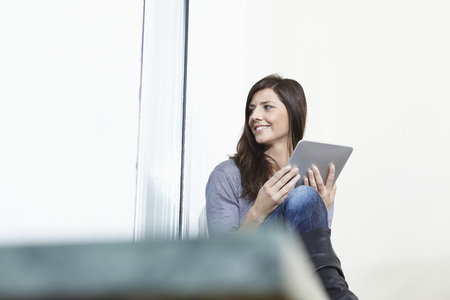 Germany,Cologne,Mid Adult Woman At Window With Digital Tablet,Smiling LANG_EVOIMAGES