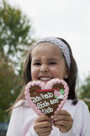 Germany,Bavaria,Huglfing,Girl Holding Gingerbread Heart In Garden,Smiling,Portrait