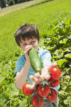 Germany,Bavaria,Boy Playing Vegetables In Garden,Smiling,Portrait LANG_EVOIMAGES