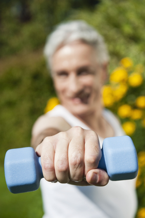 Germany,Bavaria,Mature Man Doing Exercise With Dumbbells LANG_EVOIMAGES