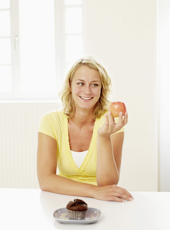 Mid Adult Woman Deciding Between Muffin And Apple