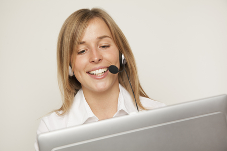 Young Woman With Headset Using Computer,Smiling