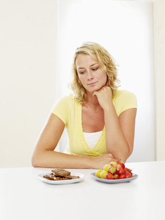 Mid Adult Woman Deciding Between Chocolate And Fruits