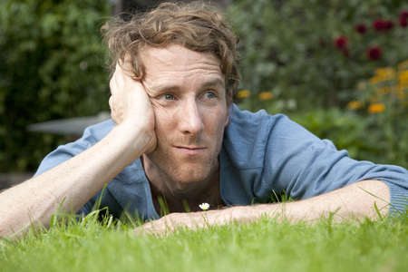 Man Thinking While Lying On Grass In Front Of Daisy
