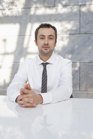 Germany,Leipzig,Businessman Sitting At Desk,Portrait LANG_EVOIMAGES