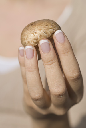 Germany,North Rhine Westphalia,Dusseldorf,Young Woman Holding Mushroom