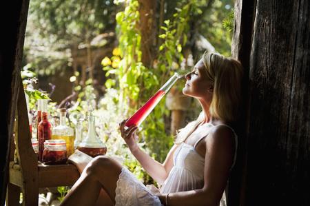 Austria,Salzburg,Flachau,Young Woman Smelling Herbal Oil LANG_EVOIMAGES