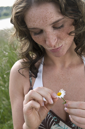 Germany,North Rhine Westphalia,Duesseldorf,Young Woman Plucking Petals Of Flower