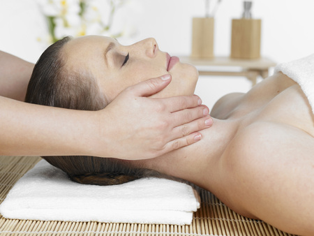 Masseur Giving Young Woman Face Massage At Spa