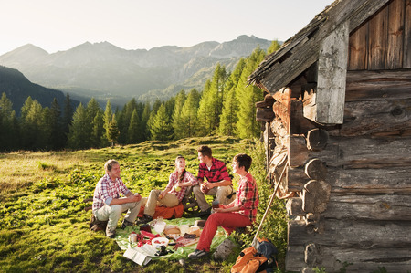 Austria,Salzburg County,Men And Women Having Picnic Near Alpine Hut At Sunset