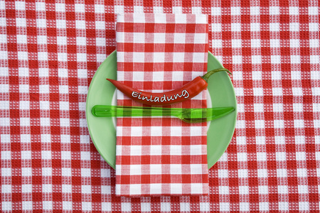 Text Invitation On Chilli With Napkin And Knife In Plate LANG_EVOIMAGES