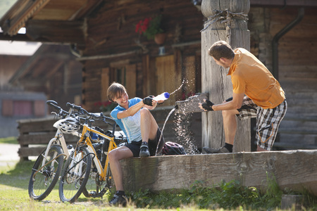 Austria,Tyrol,Man And Woman Playing With Water At Water Pump