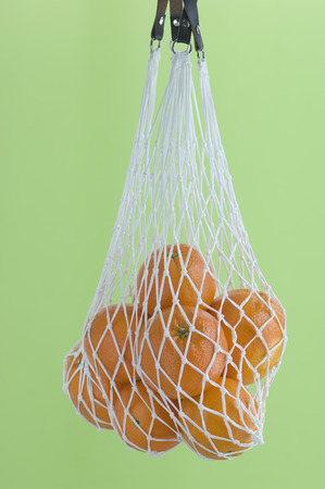 Oranges In Net Bag Against Green Background,Close Up