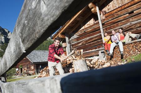 Austria,Salzburg County,Friends Looking At Man Chopping Wood Near Alpine Hut LANG_EVOIMAGES