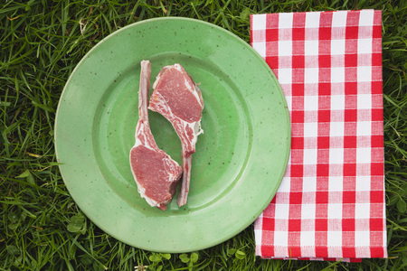 Europe,Belgium,Raw Lamb Chops In Plate With Tea Towel On Grass