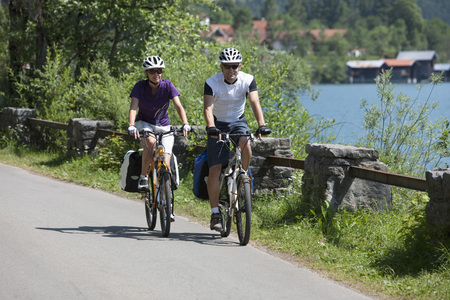 Germany,Bavaria,Man And Woman Cycling By Lake Walchensee