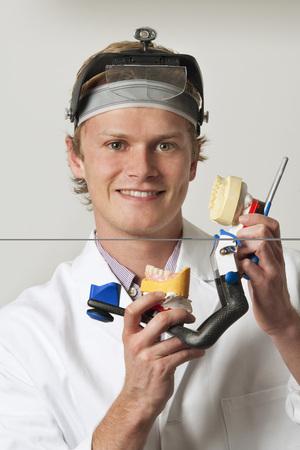 Dentist Holding Dentures In Articulator,Portrait