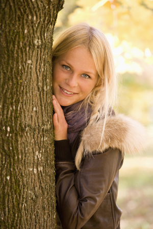 Austria,Young Woman Standing Besides Maple Tree In Autumn LANG_EVOIMAGES
