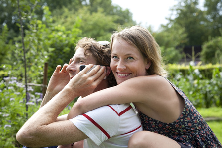 Germany,Hamburg,Man With Mobile Phone,Woman Embracing Man In Allotment Garden