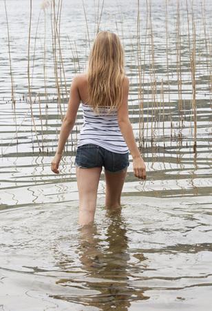 Austria,Teenage Girl Walking In Mondsee Lake