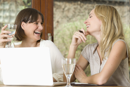 Germany,North Rhine Westphalia,Women Sitting At Table With Laptop,Smiling