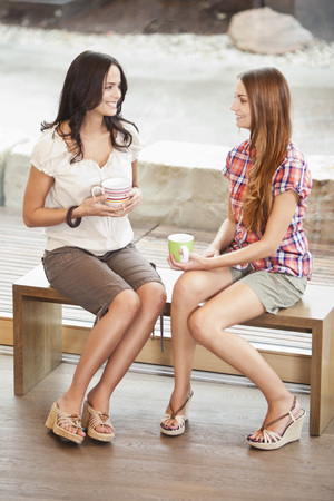 Germany,Bavaria,Young Women Sitting On Bench With Cup,Smiling