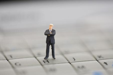 Figurine Standing On Computer Keyboard
