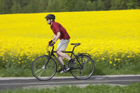 Germany,Bavaria,Starnberg,Mature Man Cycling Through Country Road LANG_EVOIMAGES