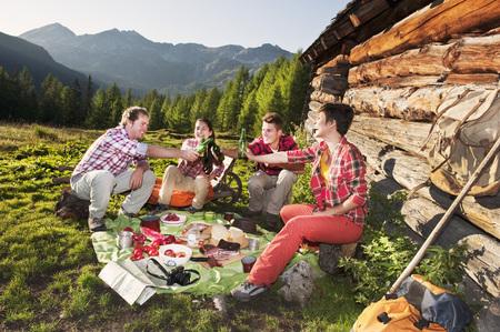 Austria,Salzburg,Men And Women Having Picnic Near Alpine Hut At Sunset