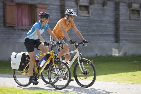 Austria,Tyrol,Man And Woman Cycling Through Road