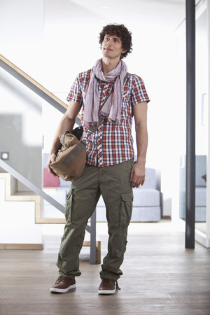 Germany,Bavaria,Young Man Standing With Bag At Home LANG_EVOIMAGES