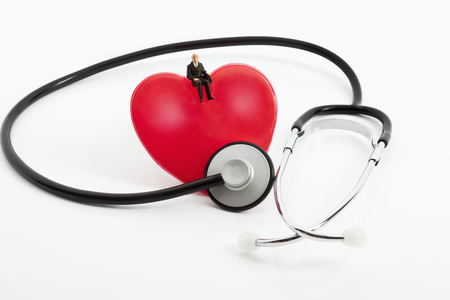 Figurine Sitting On Heart With Stethoscope On White Background LANG_EVOIMAGES