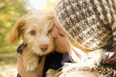 Austria,Young Woman Kissing Dog In Autumn,Close Up