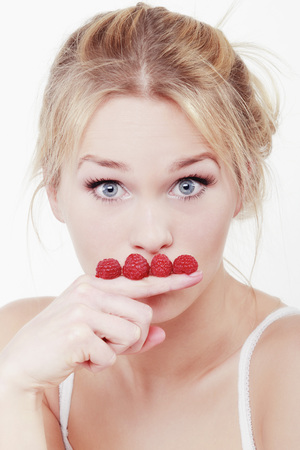 Young Woman Making Moustache With Raspberries On Her Finger,Portrait LANG_EVOIMAGES