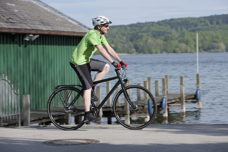 Germany,Bavaria,Starnberg,Mature Man Cycling By Pier LANG_EVOIMAGES