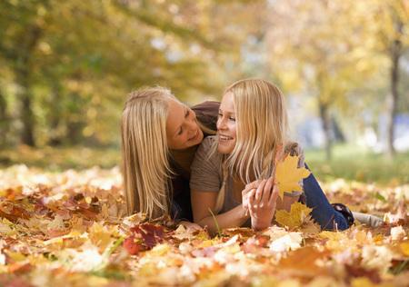 Austria,Sisters Lying On Autumn Leaf,Smiling