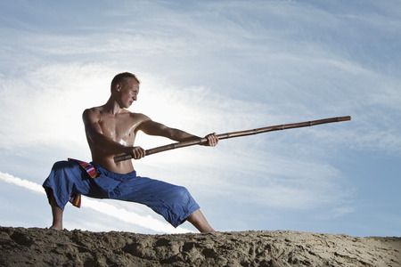Germany,Bavaria,Young Man Doing Martial Arts Training With Stick LANG_EVOIMAGES