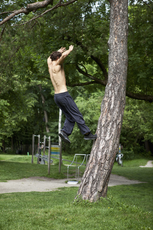 Germany,Bavaria,Young Man Doing Parcour Training In Park
