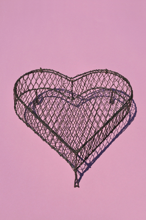 Heart Shape Cage Made By Wire On Pink Background,Close Up