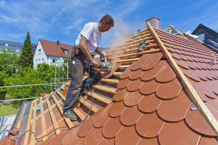 Germany,Baden-Wuerttemberg,Stuttgart,Mid Adult Man Cutting Roof Tile