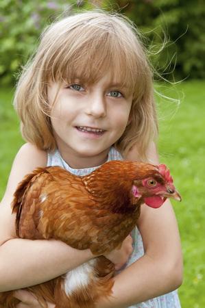 Germany,Brandenburg,Girl Holding Hen,Smiling,Portrait LANG_EVOIMAGES