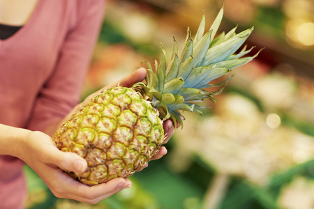 Germany,Cologne,Young Woman With Pineapple In Supermarket