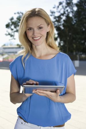 Europe,Germany,North Rhine Westphalia,Duesseldorf,Mid Adult Woman Using Digital Tablet,Smiling,Portrait