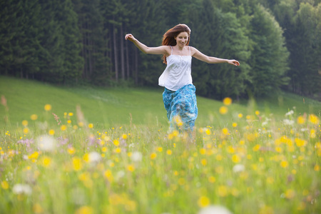Austria,Young Woman Running In Field Of Flowers LANG_EVOIMAGES