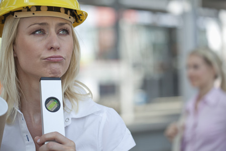 Germany,North-Rhine-Westphalica,Duesseldorf,Architect Woman Holding Spirit Level,Another Woman In Background