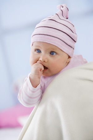 Baby Girl In Woolly Hat With Finger In Mouth,Close Up